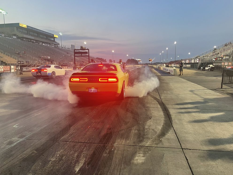 Two Challengers doing a burnout prior to drag racing