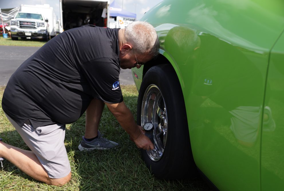 Man checking tire pressure before a drag race