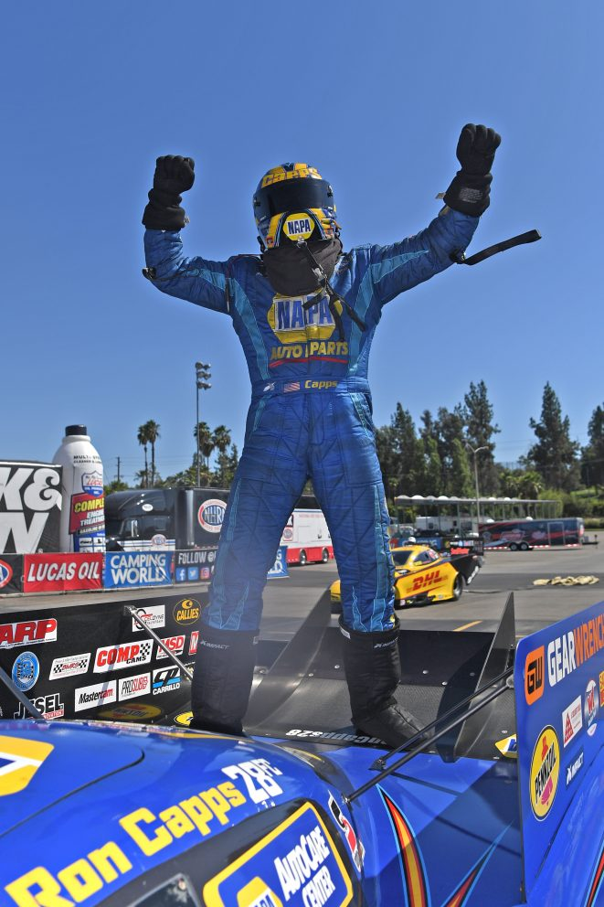 Ron Capps standing on his car in celebration after a win