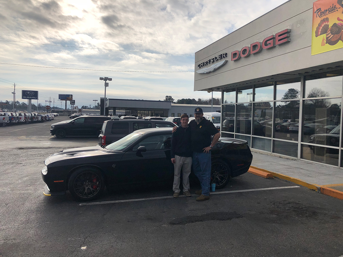 Two men with a Dodge Challenger at a dealership