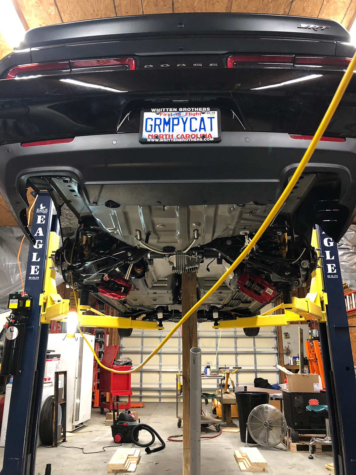Dodge Challenger lifted in a garage