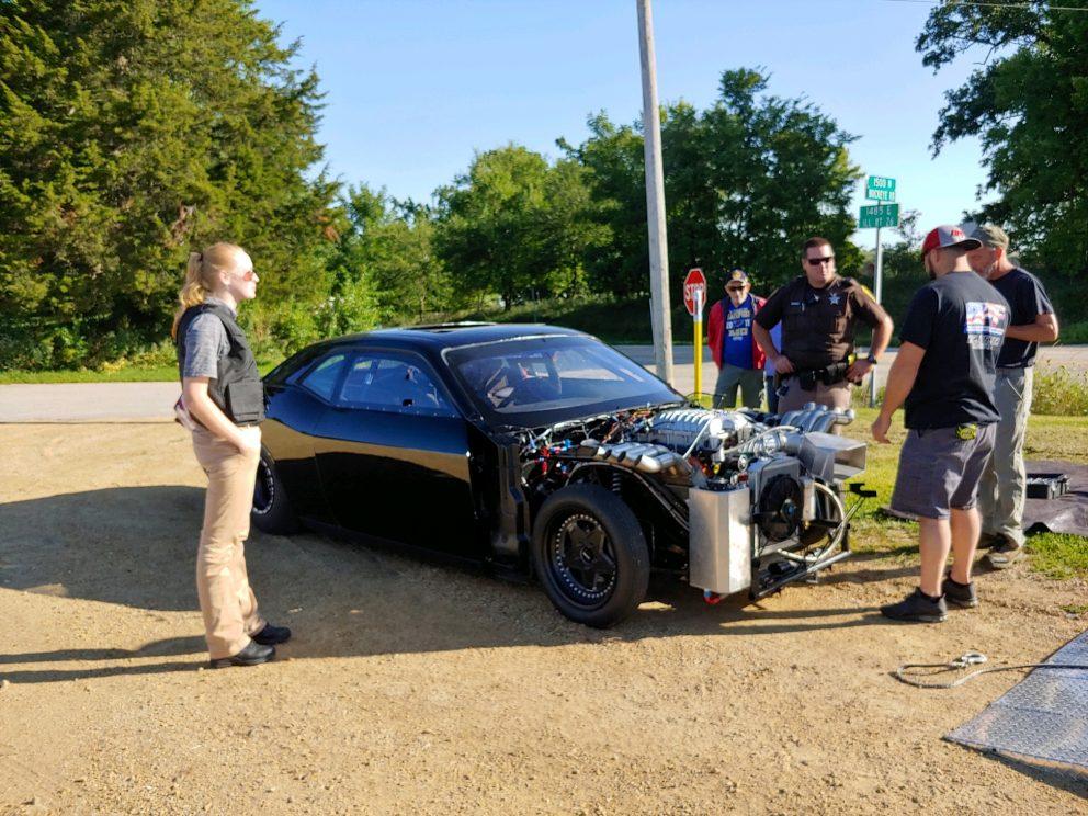 People standing around a Dodge Challenger