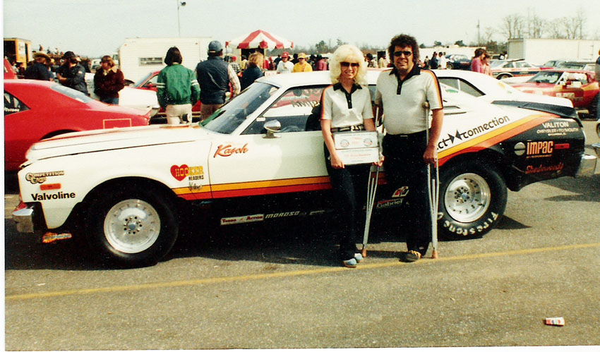 Man and woman standing in front of a drag car