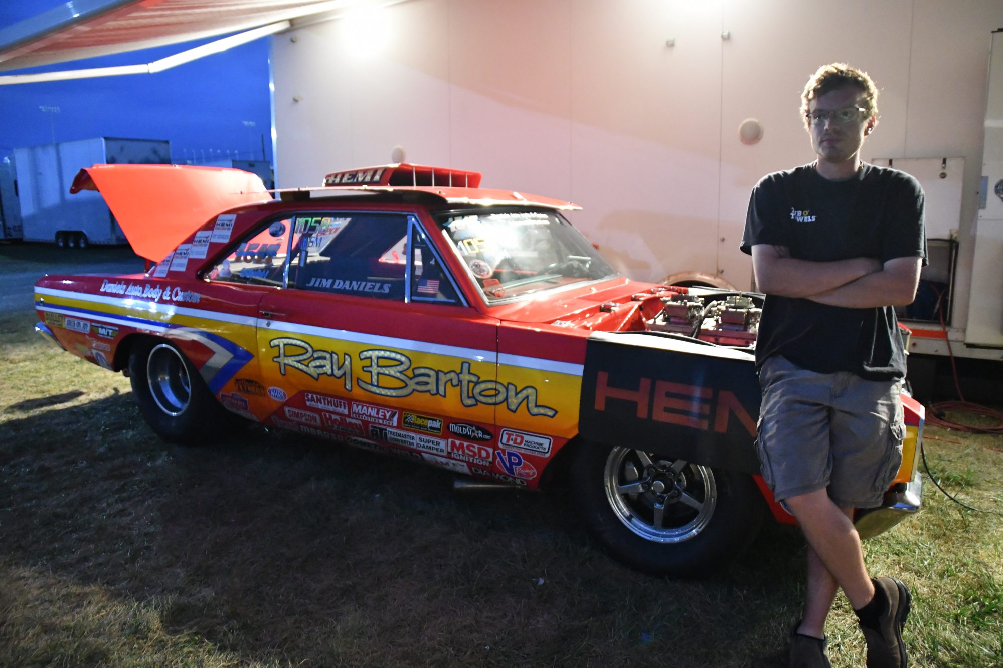 Man standing in front of his race car