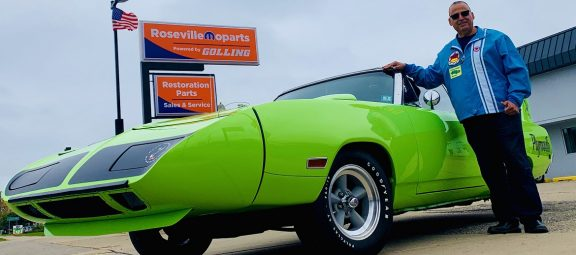 Man standing next to Plymouth Road Runner