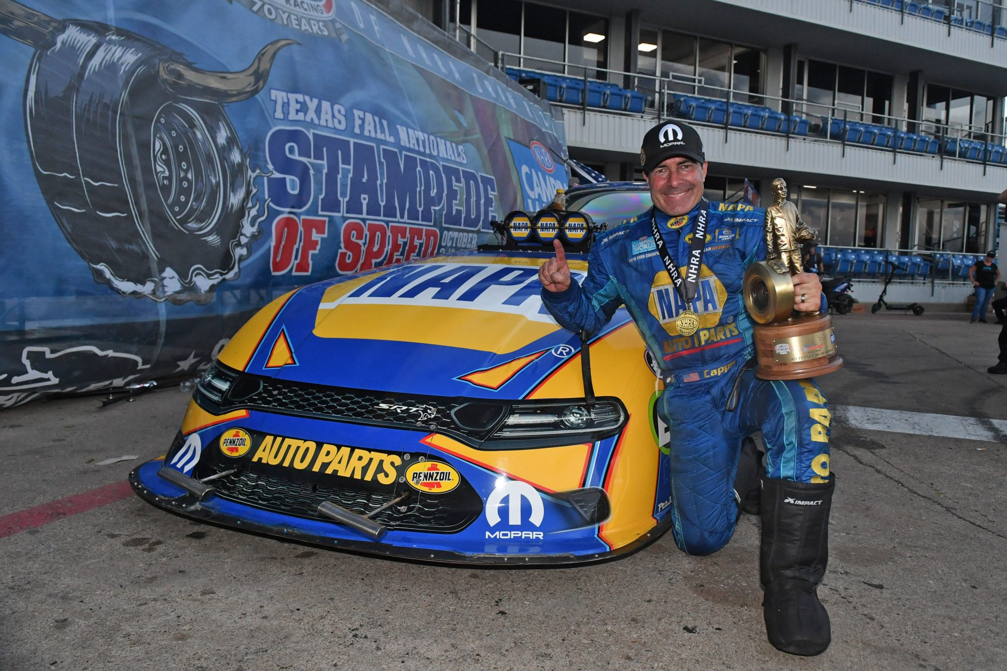 Ron Capps holding a Wally trophy after a win